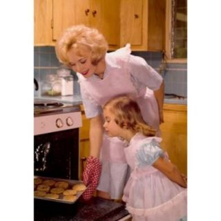 Mid adult woman putting cookies in an oven with her daughter standing beside her Poster Print (18 x 24)